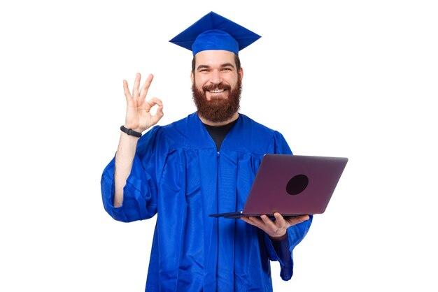 Uomo sorridente e allegro dell'allievo in veste blu che mostra ok e che tiene il computer portatile