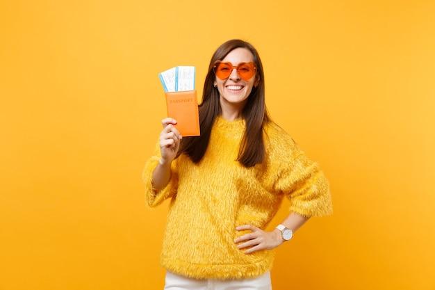 Sorridente giovane donna allegra in maglione di pelliccia, occhiali a cuore arancione con passaporto, biglietti per la carta d'imbarco isolati su sfondo giallo brillante. persone sincere emozioni, stile di vita. zona pubblicità.