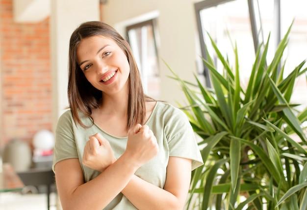 Sorridendo allegramente e festeggiando con i pugni chiusi e le braccia incrociate sentendosi felice e positivo