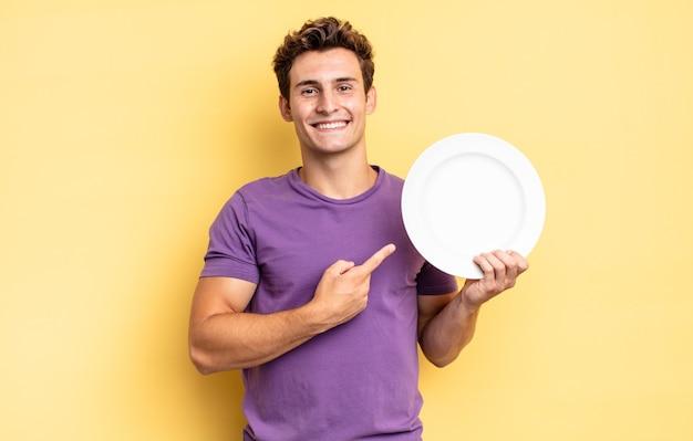 Sorridere allegramente, sentirsi felici e puntare di lato e verso l'alto, mostrando l'oggetto nello spazio della copia. concetto di piatto vuoto