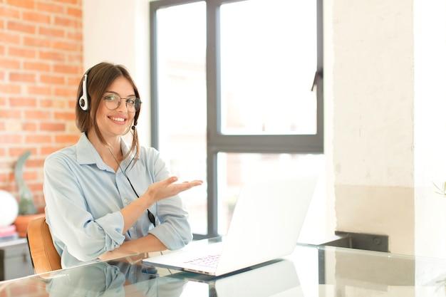 Sorridendo allegramente, sentendosi felice e mostrando un concetto nello spazio della copia con il palmo della mano