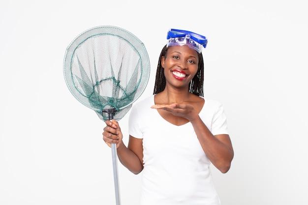 Sorridere allegramente, sentirsi felici e mostrare un concetto con occhiali e rete da pesca