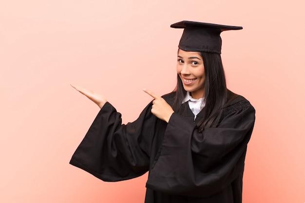 Sorridendo allegramente e indicando di copiare spazio sul palmo sul lato, mostrando o pubblicizzando un oggetto