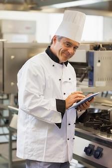 Cuoco unico sorridente che per mezzo della compressa digitale