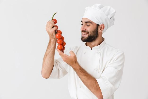 Sorridente capo uomo in uniforme tenendo i pomodori durante la cottura insalata di verdure isolate su muro bianco