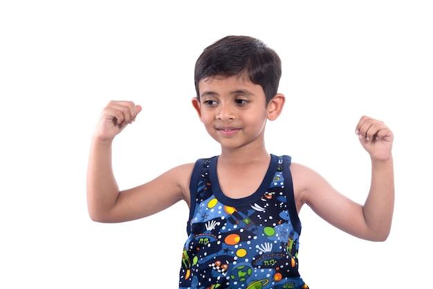Ragazzo sorridente del bambino che mostra la sua forza dei muscoli bicipiti della mano su priorità bassa bianca.