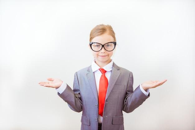 Ragazza sorridente del bambino che indica il suo dito indice a qualcosa su priorità bassa bianca. successo, concetto di business creativo e innovazione