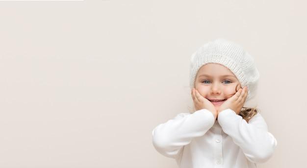 Bambino sorridente in fatti a mano a maglia di lana fascia e maglione bianco isolato su sfondo beige