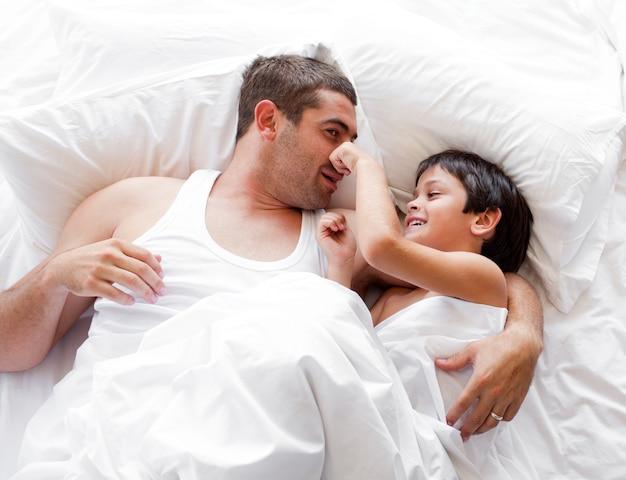 Bambino sorridente che gioca con suo padre che si trova su un letto a casa