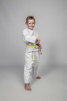 Bambino sorridente che pratica arti marziali con un bokken di legno.