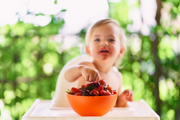 Il bambino sorridente prende la frutta in una ciotola sul tavolo