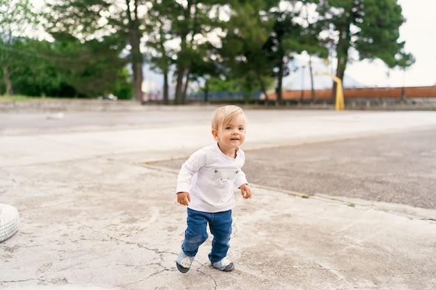 Il bambino sorridente sta su un campo da giuoco concreto