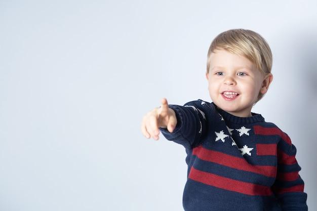 Il bambino sorridente in un maglione con una bandiera americana degli stati uniti sta indicando qualcosa su uno sfondo bianco