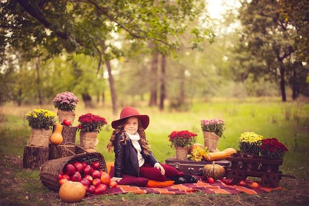 Il bambino sorridente con il cestino delle mele rosse che si siedono in autunno parcheggia