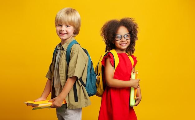 Bambini sorridenti con zaini scolastici che tengono in mano libri e matite