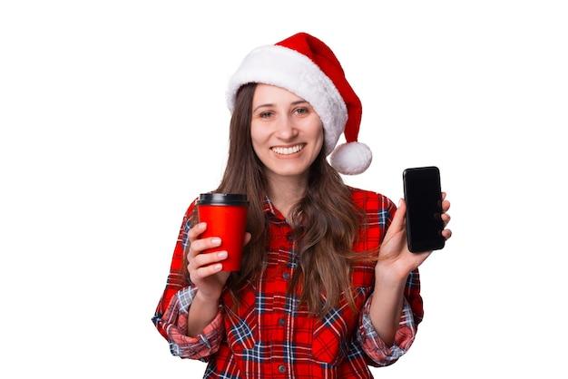 Sorridente donna natalizia sta mostrando lo schermo del suo telefono alla telecamera.