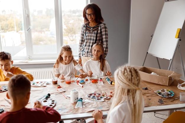 Compagni di classe sorridenti che dipingono su carta con vernici colorate a scuola