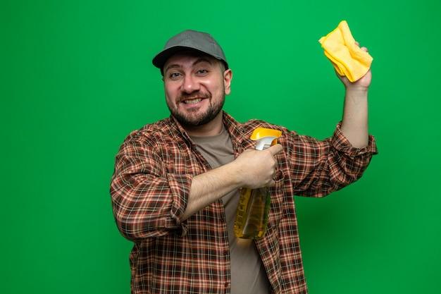 Uomo addetto alle pulizie sorridente che tiene in mano panni per la pulizia e detergente spray