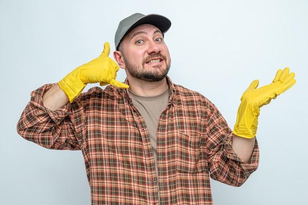 Sorridente uomo più pulito con guanti di gomma che tiene la mano aperta e gesticola chiamami segno