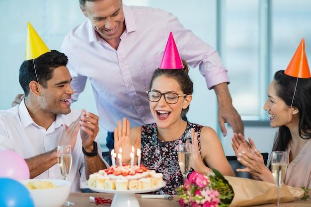Colleghi sorridenti che celebrano il compleanno della donna
