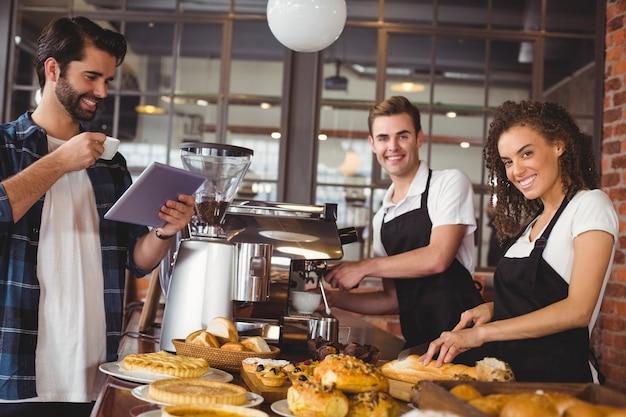 Colleghi sorridenti che servono cliente con tablet e caffè