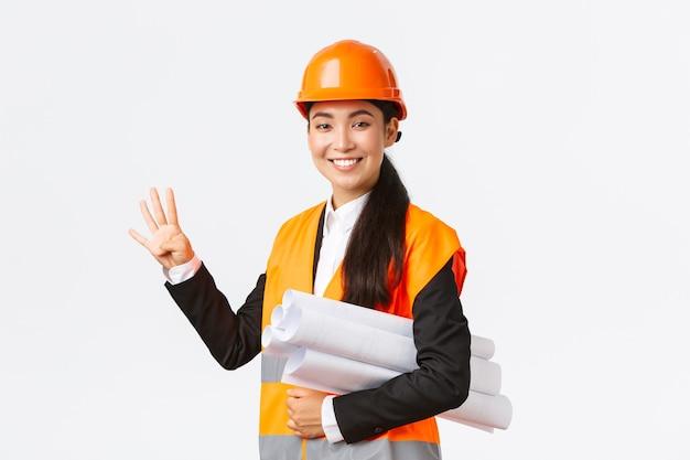 Sorridente ingegnere asiatico fiducioso, direttore della costruzione in casco di sicurezza, porta progetti, mostrando quattro dita, assicura che la costruzione sia finita in tempo, in piedi sfondo bianco ottimista