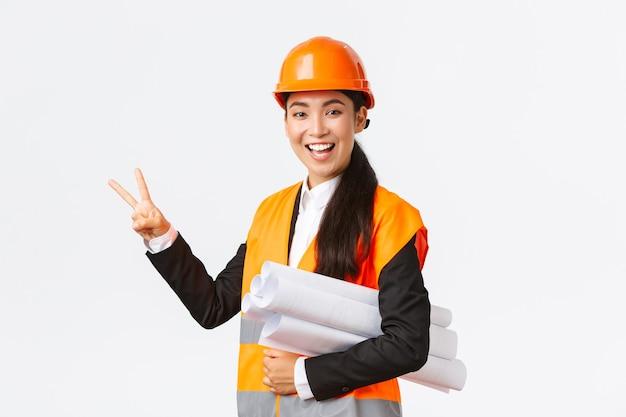 Sorridente ingegnere asiatico fiducioso, direttore della costruzione in casco di sicurezza, porta progetti, mostrando due dita, assicura che la costruzione sia finita in tempo, in piedi su sfondo bianco ottimista