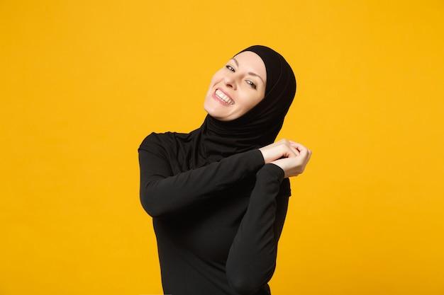 Sorridente fiduciosa bella giovane donna musulmana araba in abiti neri hijab in posa isolata sulla parete gialla, ritratto. concetto di stile di vita dell'islam religioso della gente.