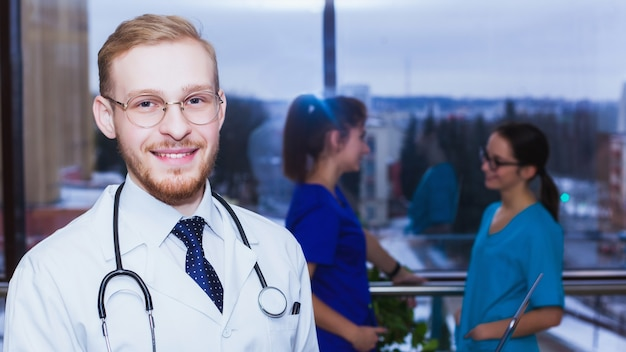 Sorridente medico fiducioso alla reception, personale medico che lavora sullo sfondo