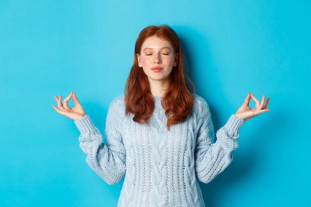 Sorridente ragazza fiduciosa con i capelli rossi che rimane paziente, tenendosi per mano in zen, posa di meditazione e fissando la telecamera, pratica yoga, calma in piedi su sfondo blu.