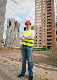 Sorridente lavoratore fiducioso in casco e giubbotto di sicurezza in piedi sul cantiere