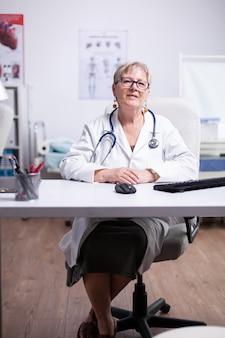 Sorridente fiducioso giovane dottoressa adulta primo piano ritratto, amichevole donna felice medico o infermiere medico generico professionista in posa con stetoscopio guardando la fotocamera in studio medico