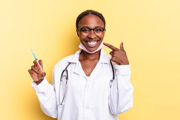 Sorridere con sicurezza indicando il proprio ampio sorriso, atteggiamento positivo, rilassato, soddisfatto. medico e concetto di siringa