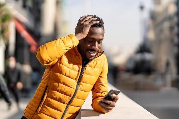 Uomo africano confuso sorridente con il telefono cellulare che si lamenta dell'errore che si siede in una città
