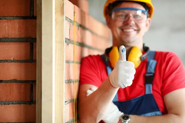 Lavoratore sorridente del cantiere che lavora al progetto
