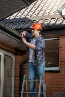 Operaio edile sorridente sulla scala a pioli sotto il tetto della casa