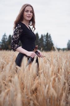 Violinista felice giovane donna sorridente su un bellissimo campo