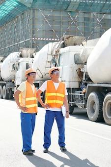 Appaltatori sorridenti che camminano lungo le file di autobetoniere e pianificano la giornata lavorativa al cantiere...