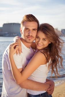 Coppie sorridenti che abbracciano alla spiaggia