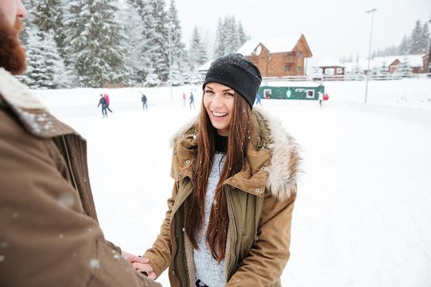 Coppia sorridente che si diverte all'aperto con la neve sullo sfondo