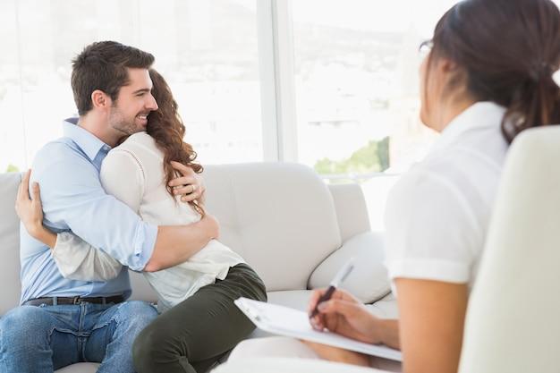 Sorridente coppia abbracciarsi davanti al loro terapeuta