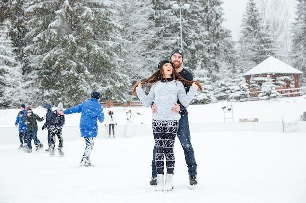 Coppia sorridente in pattini da ghiaccio che si abbracciano all'aperto con la neve sullo sfondo