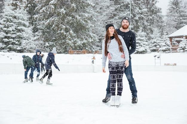 Coppia sorridente in pattini da ghiaccio in piedi all'aperto