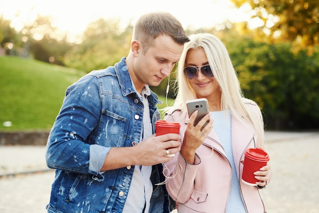 Coppie sorridenti nell'amore che cammina nel parco di autunno, tenentesi per mano. ascolta la musica in cuffia e bevi caffè per andare.