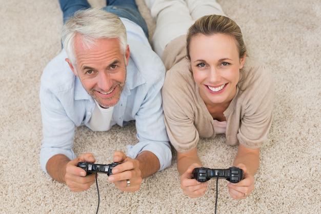 Coppie sorridenti che si trovano sulla coperta che gioca i video giochi