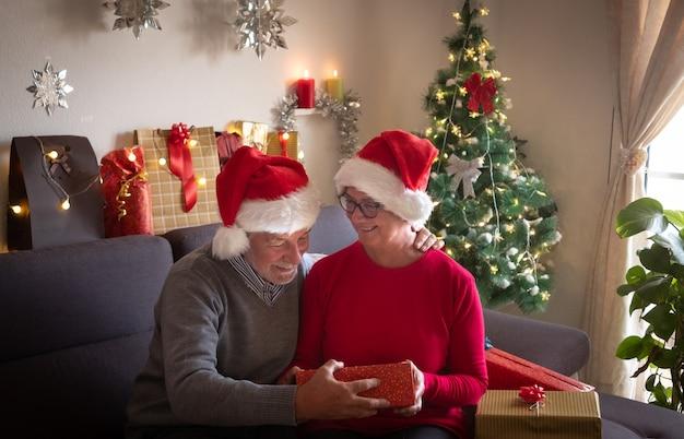 Una coppia sorridente di un uomo e una donna con i cappelli di babbo natale aprono un regalo di natale e sono sorpresi dal contenuto. albero di natale e regali per la famiglia che li circonda