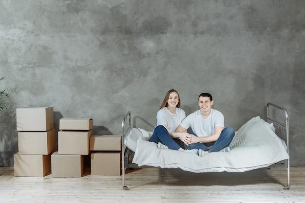 Sorridente coppia uomo e donna seduta sul letto tra scatole nel nuovo appartamento