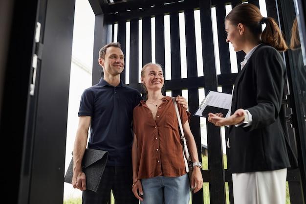 Coppia sorridente incontro agente immobiliare