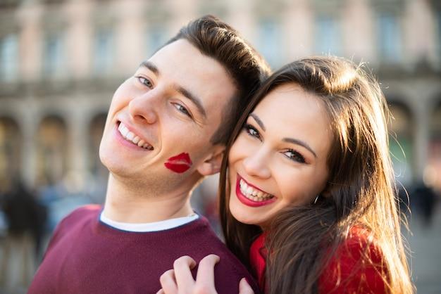 Ritratto sorridente delle coppie, l'uomo ha un segno di bacio del rossetto sulla sua guancia