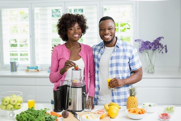Coppie sorridenti che preparano il frullato della fragola in cucina a casa